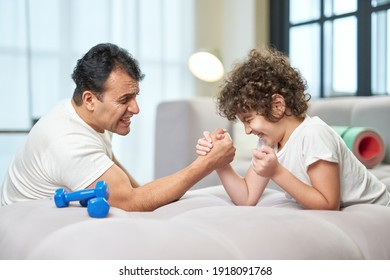 Cute latin boy trying to win while having fun, playing armwrestling together with his father at home lying on the couch