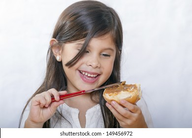 Cute latin girl with long hair smiles as bread smeared with peanut butter