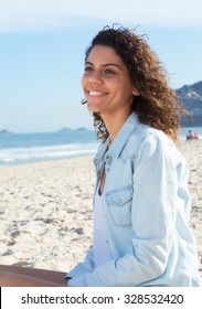 Cute latin woman with curly hair dreaming at beach