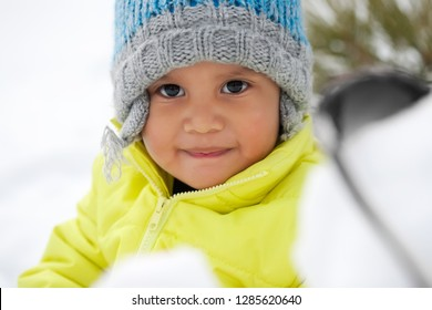 Cute Latino toddler smiling while playing in the snow during winter and wearing a knit hat.