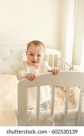 Cute laughing 10 month baby standing in a white crib