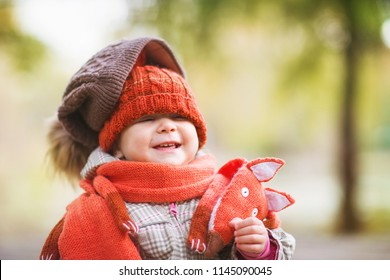 cute laughing baby in autumn clothes. child in knitted hats and scarf. orange animal is fox. concept: warm clothing, cold weather