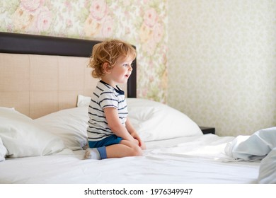 Cute laughing child boy sits in bed. Boy plays at home. Child in a sunny bedroom.