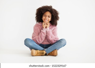 Cute laughing girl in casual clothes sitting against white background