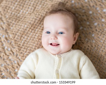 Cute laughing little baby in a warm sweater on a brown knitted blanket