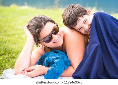 Cute laughing school boy enjoying his summer holidays with his mom lying on the grass after swimming in the mountain lake. Family fun, joy, togetherness or Happy Mother's Day concepts background.