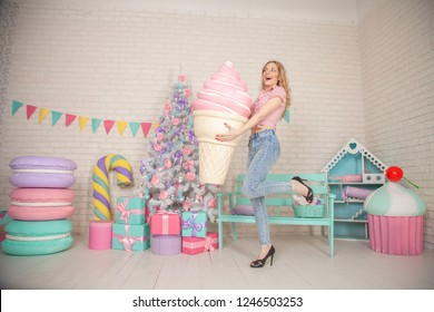 cute laughing slim girl in shirt and jeans posing with her favorite huge pink ice cream in a waffle Cup and enjoying life on the background of white Christmas tree with gifts