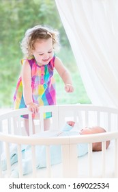Cute laughing toddler girl playing with her newborn baby brother laying in a white round crib next to a big window with garden view