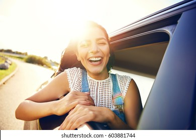 Cute laughing young woman hanging out her head from a car through the open window enjoying the freedom of the breeze in her hair as it travels along a rural road