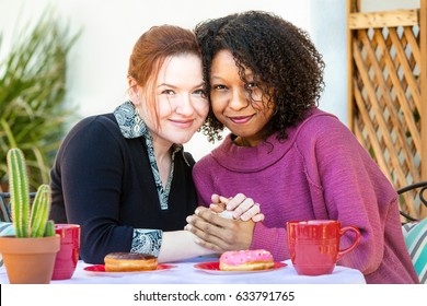 Cute lesbian couple holding hands while seated together at cafe