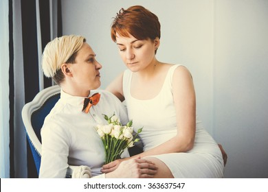 Cute lesbian couple in wedding outfits sitting in the armchair. Gay marriage concept.. Toned picture