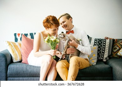 Cute lesbian couple in wedding outfits sitting with their cat. Gay marriage concept. Selective focus