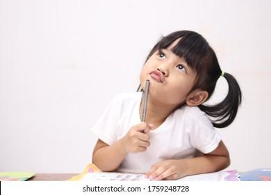 Kleines asiatisches Mädchen, das Stift und Buch hält, studiert und lernt, während es denkt oder eine gute Idee hat, lächelt und schaut hoch, Fantasie mit Kopienraum