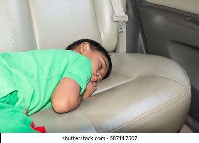 cute litte boy sleeping in car