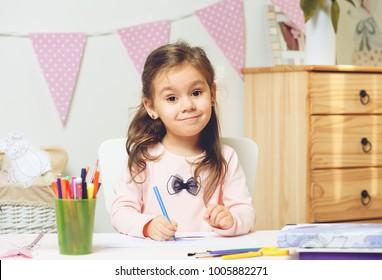 Cute litter girl painting or doing her homework in her room