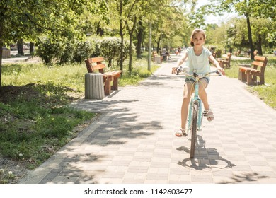 Cute little 10 years old girl in casual outfit playing at park in warm summer day. She having fun riding a bicycle