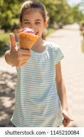 Cute little 10 years old girl in casual outfit playing at park in warm summer day. She have fun licking an ice cream in  a waffle cup. Copy space