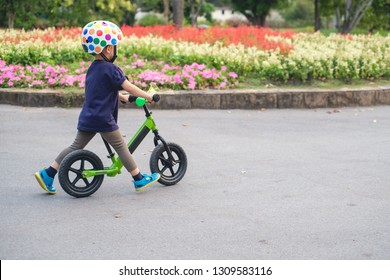 Cute little 2 - 3 years old toddler boy child wearing safety helmet learning to ride first balance bike in sunny summer day, kid cycling at park, Explore & Appreciate Nature with toddlers concept