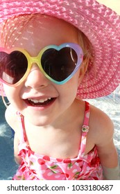 A cute little 2 year old toddler girl is sitting outside at the pool in a swimming suit, sun hat, and heart shaped sunglasses, laughing as she happily looks at the camera.