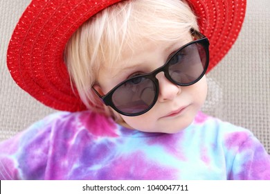 A cute little 2 year old toddler girl is sunbathing outside, wearing a red summer hat and dark sunglasses, as she loos at the camera making a serious face.