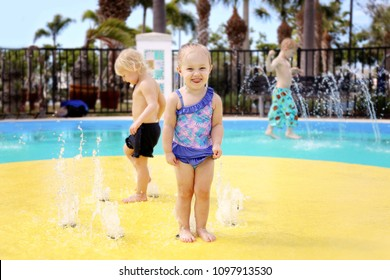 A cute little 2 year old toddler girl is laughing as she plays outside in a water splash park with her friends on a hot summer day.