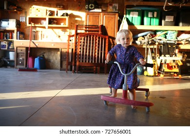 A cute little 2 year old toddler girl wearing a dress is riding a red ride-on scooter type bicycle in her home garage.