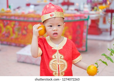 Cute little 2 years old Asian toddler baby boy child in traditional red Chinese suit holding sacred orange at local Chinese temple , Happy Chinese new year celebrations, Lunar New Year concept
