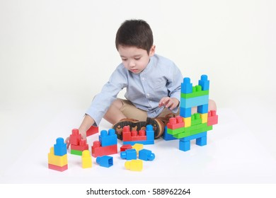 Cute little 4 year old boy playing with colorful stacking bricks.  White background.