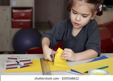 Cute little 5 years old girl making something crafted with colored paper, scissors and match boxes, to create fun and easy with children, concept for preschool and kindergarten