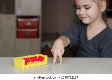 Cute little 5 years old girl playing with crafted sofa made with colored paper and match boxes, to create fun and easy with children, concept for preschool and kindergarten