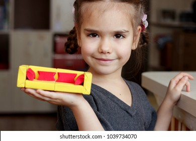 Cute little 5 years old girl holding crafted sofa made with colored paper and match boxes, to create fun and easy with children, concept for preschool and kindergarten