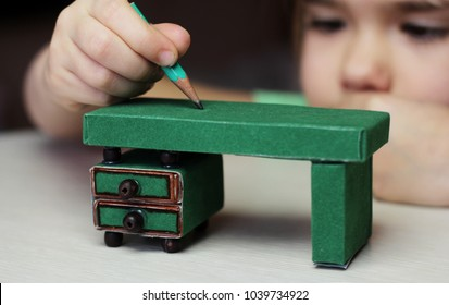 Cute little 5 years old girl writing with a miniature pencil over the crafted desk made with colored paper and match boxes, to create fun and easy with children, concept for preschool and kindergarten