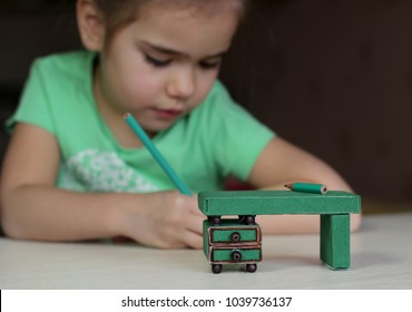 Cute little 5 years old girl writing with a pencil near the crafted desk made with colored paper and match boxes, to create fun and easy with children, concept for preschool and kindergarten