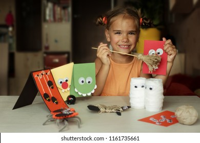 Cute little 5-6 years old girl sitting near different crafted Halloween decorations, create fun and easy with children, diy for Halloween concept