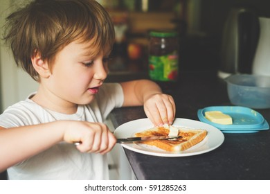 Cute little 6 year old boy preparing alone his toast with butter