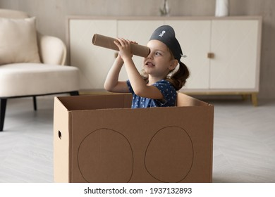 Cute little 7s Caucasian girl child in pirate hat look in spyglass have fun playing at home. Small kid sit in toy ship engaged in funny game activity. Entertainment concept.