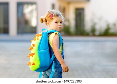 Cute little adorable toddler girl on her first day going to playschool. Healthy upset sad baby walking to nursery school. Fear of kindergarten. Unhappy child with backpack on the city street, outdoors
