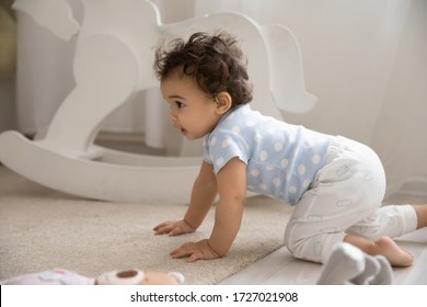 Cute little african American baby infant go on hands and knees on cozy warm wooden floor with carpet, small biracial toddler child girl boy learn walking creeping on fours at home, childcare concept