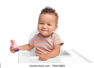 Cute little African American baby with nibbler on white background