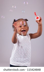 Cute little African American girl playing with soap bubbles