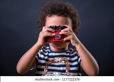 Cute little african american girl using a toy camera to take pictures