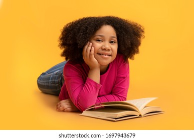 Cute Little African American Girl Reading Book On Floor In Studio And Smiling At Camera, Lying On Yellow Background, Free Space