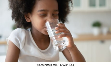 Cute little African American girl drink clean still mineral water from glass at home, small funny biracial child feel thirsty, enjoy clear aqua for daily refreshment, healthy lifestyle concept