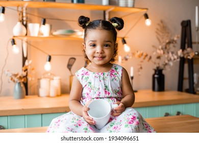 cute little african american girl at home in the kitchen