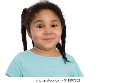 Cute little African American girl with her curly hair in braids looking at the camera with a sweet impish smile, head and shoulders on white with copyspace