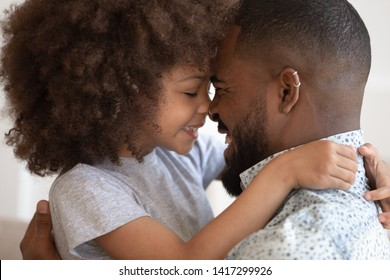 Cute little african child girl embrace touch noses with happy single black dad, loving mixed race family father and small kid daughter hug bond cuddle enjoy moment of affection, close up side view
