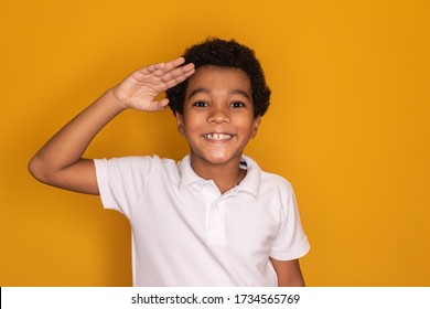 Cute little afro child boy showing a saluting gesture on yellow background. Human emotions and facial expression