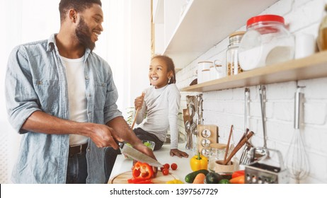 Cute little afro girl and her dad cooking in kitchen at home. Happy family cooking concept