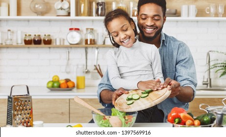 Cute little afro girl and his father making salad together. Happy childhood concept, copy space