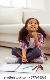 Cute little Afro-American girl in casual clothes drawing, dreaming and smiling while sitting near the sofa in the room.